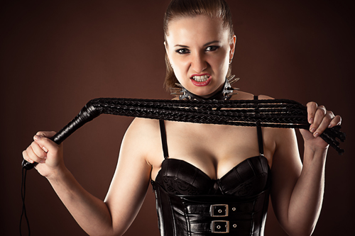 angry mistress with a whip in hands